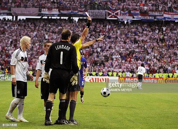 Belgian referee Frank de Bleeckere gives a red card to German midfielder Bastian Schweinsteiger next to German defender Philipp Lahm and German...