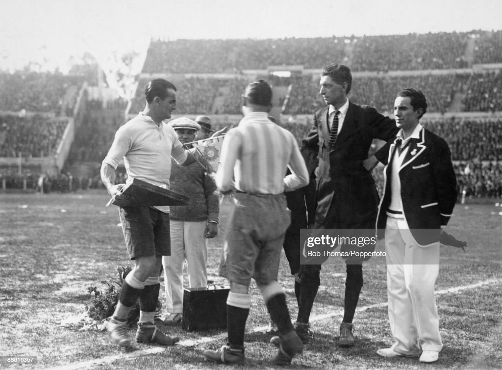 Belgian referee Jean Langenus (wearing a tie) presides over the pre-match formalities as Uruguayan captain Jose Nasazzi (left) exchanges pennants with Argentina's Manuel Ferreira prior to the FIFA World Cup Final at the Estadio Centenario in Montevideo, 30th July 1930. Uruguay defeated Argentina 4-2 to win the Jules Rimet Trophy.
