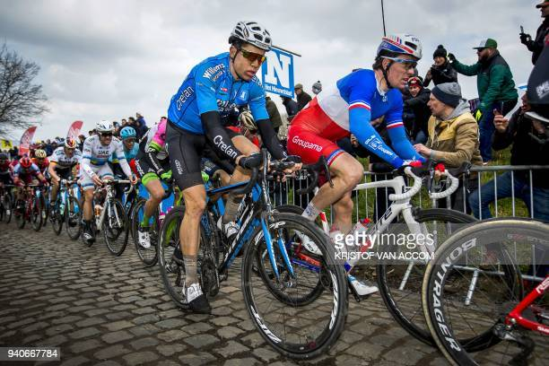 Belgian rider Wout van Aert of team Verandas Willems Crelan and French rider Arnaud Demare of team FDJ pedal up the 'Oude Kwaremont' hill in...