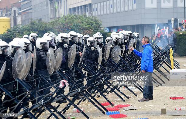 Belgian riot police stand behind security fencing as a man gestures towards them during a protest by European farmers blocking access to the European...