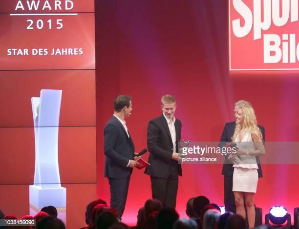 Belgian soccer player Kevin De Bruyne of German soccer club VfL Wolfsburg receives the 'Star of the year'Sport BILDAward next to hosts Alexander...