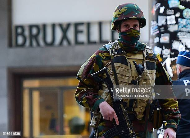 A Belgian soldier patrols outside Brussels Central Station as people are allowed in small groups of ten to reach the station in order to take their...