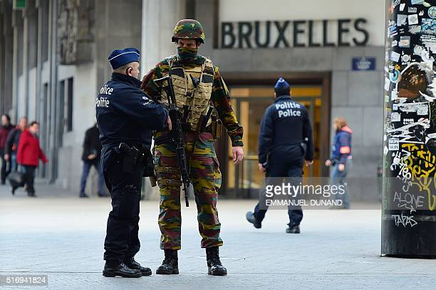 Belgian soldier speaks to a police officer outside Brussels Central Station as people are allowed in small groups of ten to reach the station in...