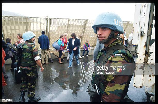 Belgian soldier stands guard as civilian families evacuate April 11, 1994 from Kigali, Rwanda. The majority of French and Belgian nationals living in...