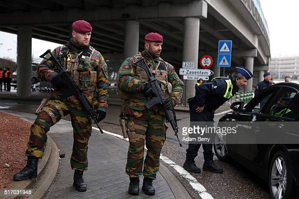 Belgian soldiers stand guard as police check vehicles outside of the closed Brussels Zaventem airport on March 23 2016 in Brussels Belgium Belgium is...