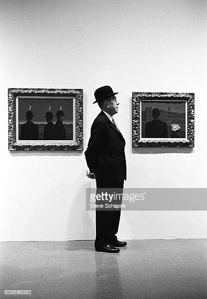 Belgian surrealist artist Rene Magritte stands in profile wearing a bowler hat between two of his paintings 'Pandoras Box' and 'The Mysteries of the...