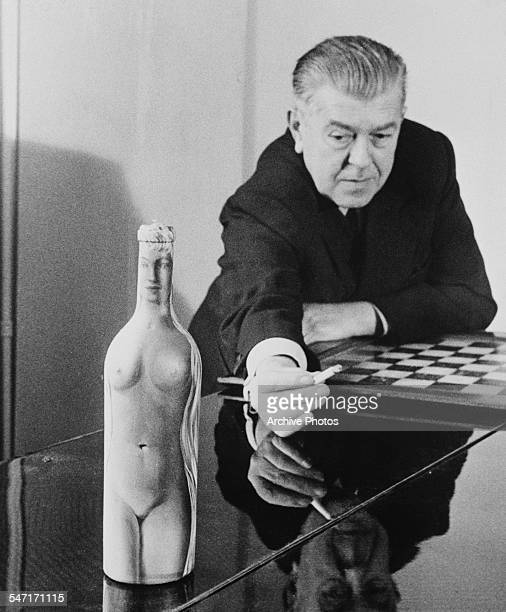 Belgian surrealist artist Rene Magritte with 'FemmeBouteille' his oil painting of a nude on a glass bottle circa 1955