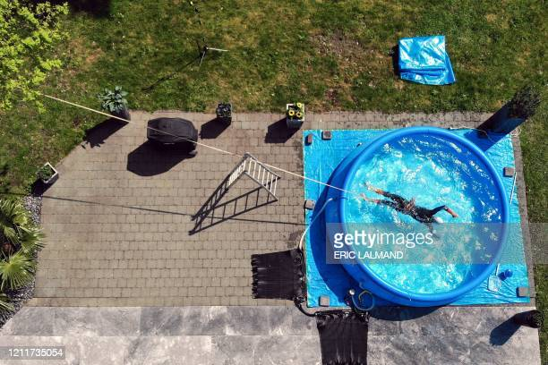 Belgian triathlete Jelle Geens works out in an inflatable swimming-pool during a reportage on the lockdown conditions of athletes' training, in...