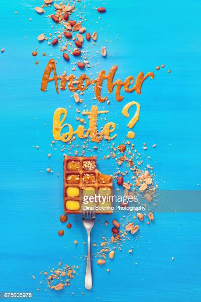 belgian waffle on a fork with lettering on a sky blue background - nut food stock photos and pictures
