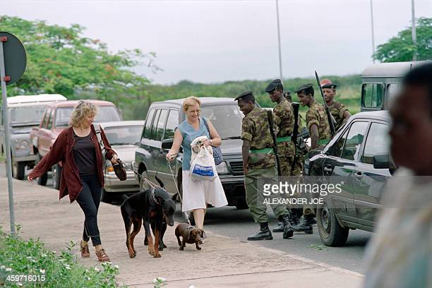 Belgian women walk their dogs to the Bujumbura Burundi airport on March 29 1995 to take the animals with them on their flight back to Brussels The...