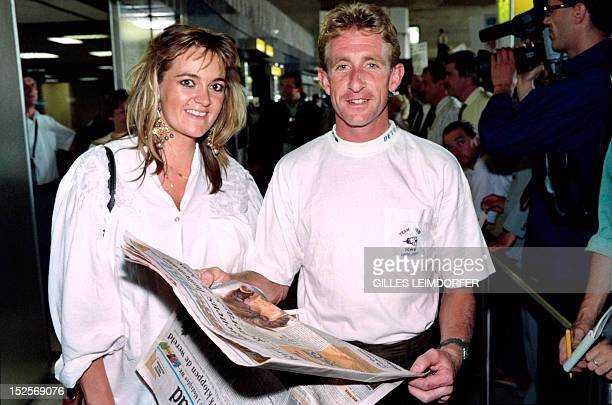 Belgian World Champion cyclist Rudy Dhaenens reads French press as he arrives with his wife at Roissy CharlesDeGaulle airport outside Paris on...