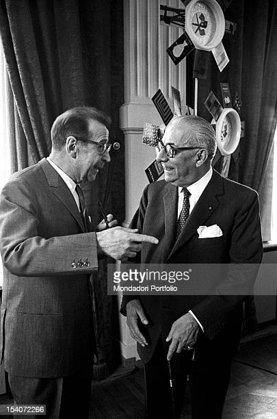 Belgian writer Georges Simenon chatting with a man. 1960s