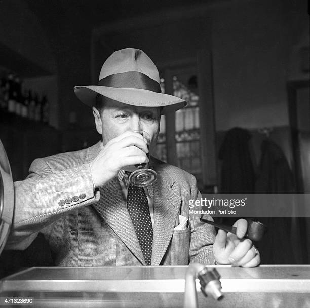 Belgian writer Georges Simenon drinking a glass of wine at the trattoria Milan 1957