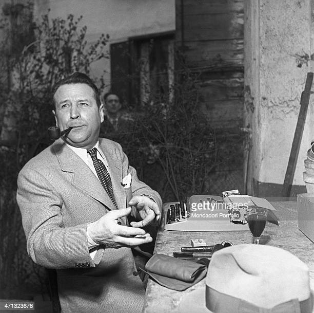 Belgian writer Georges Simenon sitting at the table in front of a typewriter. Milan, 1957