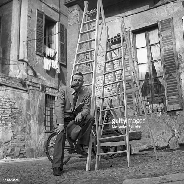 Belgian writer Georges Simenon sitting on a ladder. Milan, 1957