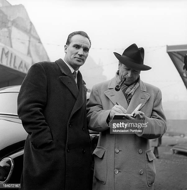 Belgian writer Georges Simenon smoking a pipe and writing something Milan 1950s