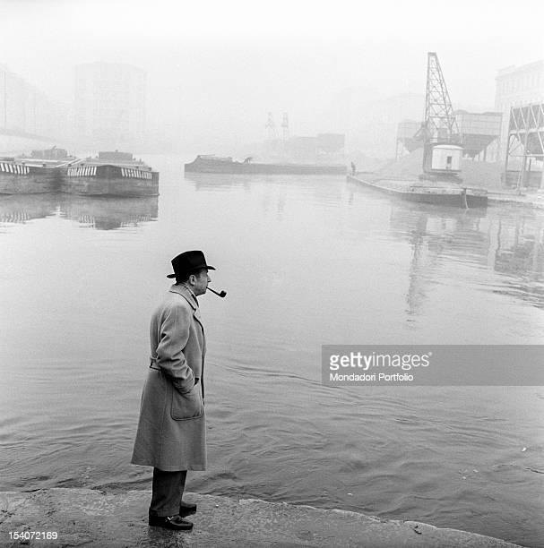 Belgian writer Georges Simenon smoking a pipe by the Navigli. Milan, 1950s