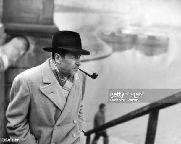 Belgian writer Georges Simenon, smoking a pipe, climbing the metal stairs on the docks of Porta Ticinese. In the background, in the mist, there are...
