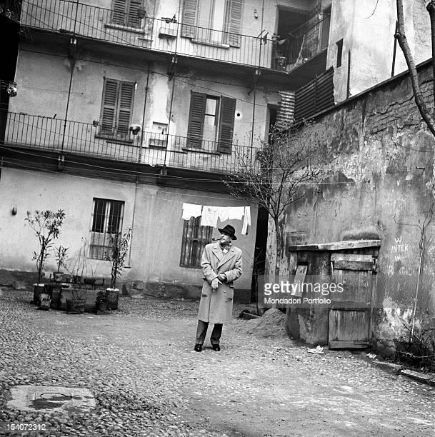 Belgian writer Georges Simenon smoking a pipe in a courtyard Milan 1950s