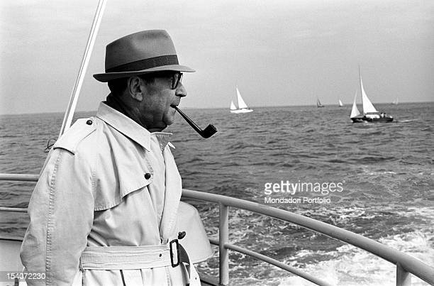 Belgian writer Georges Simenon smoking a pipe on a boat. 1966