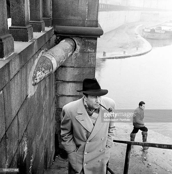 Belgian writer Georges Simenon smoking the pipe. He's going up the stairs along the Navigli. Milan, 1950s
