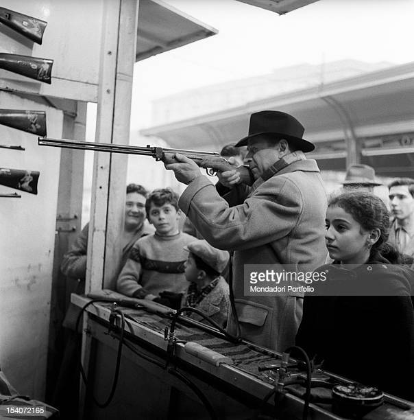 Belgian writer Georges Simenon taking part in a shooting competition at a funfair with some children. Milan, 1950s