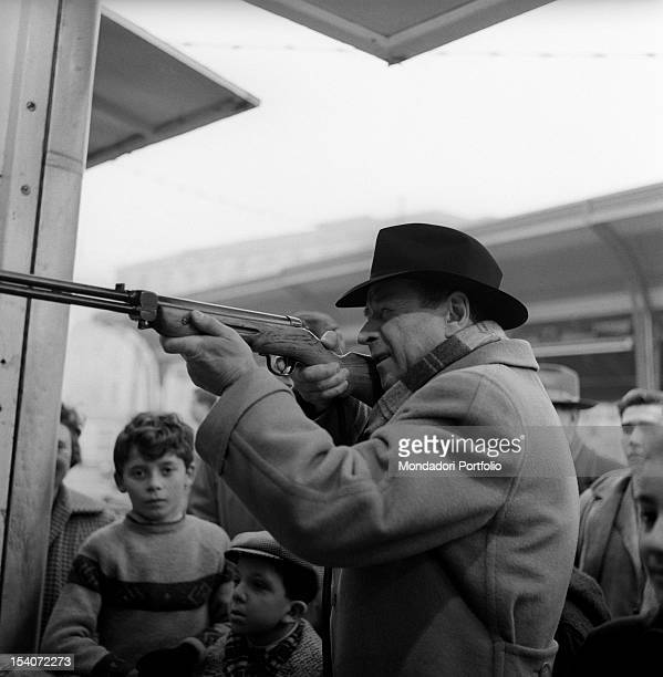 Belgian writer Georges Simenon taking part in a shooting competition at a funfair Some children are watching him Milan 1950s