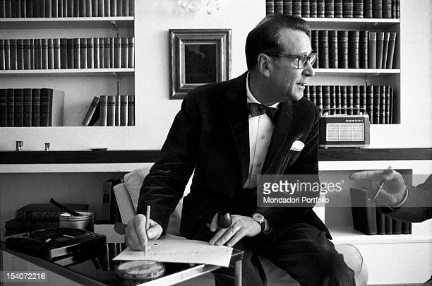 Belgian writer Georges Simenon wearing a dinnerjacket and writing 1960s