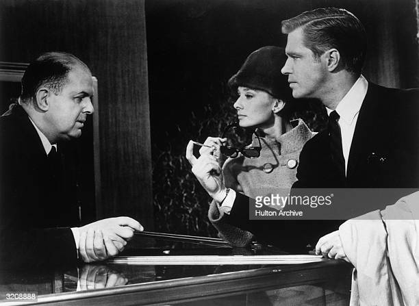 Belgianborn actor Audrey Hepburn and American actor George Peppard stand at the Tiffany's sales counter speaking with American actor John McGiver in...