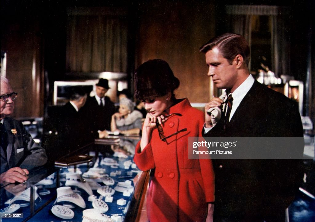 1961, Belgian-born actor Audrey Hepburn (1929 - 1993) and American actor George Peppard (1928 - 1994) browse through jewelry at Tiffany's department store in a scene from director Blake Edwards' film 'Breakfast At Tiffany's' 1961.