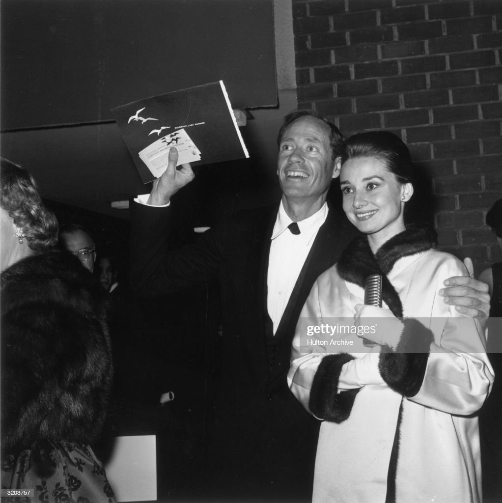 Belgian-born actor Audrey Hepburn (1929-1993) and her husband, American actor Mel Ferrer, smile at the premiere of director Joseph L. Mankiewicz's film, 'Suddenly Last Summer.' Hepburn wears a fur-lined satin coat and white gloves while clutching a small handbag.