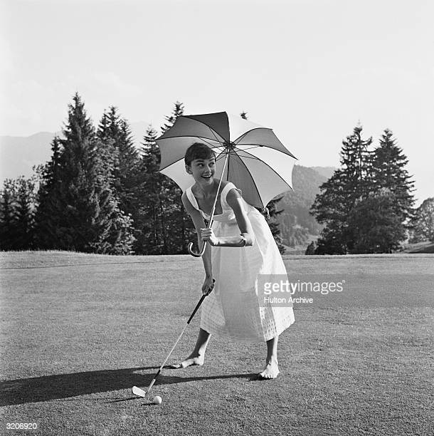 Belgianborn actor Audrey Hepburn barefoot and wearing a summer dress playing golf and holding an umbrella over her head
