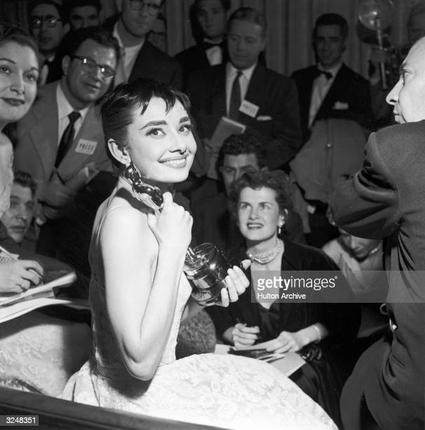 Belgianborn actor Audrey Hepburn is surrounded by reporters as she holds the Best Actress Oscar she won for her role in director William Wyler's film...