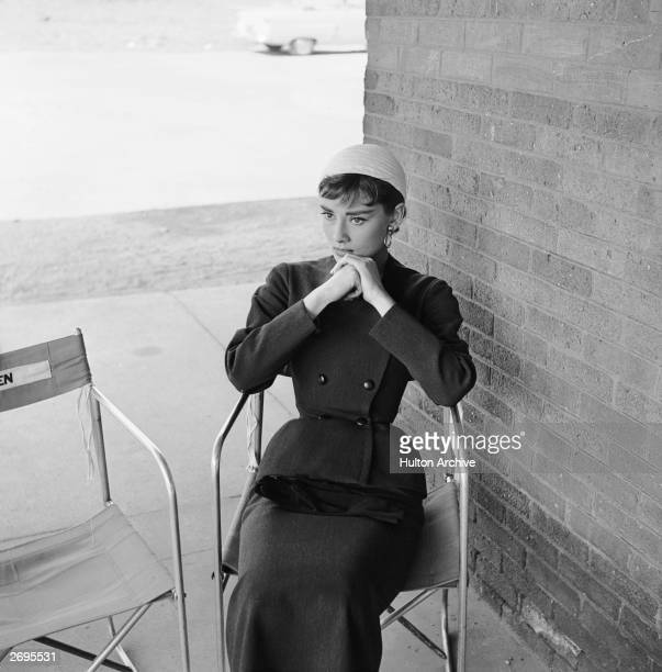 Belgian-born actor Audrey Hepburn , wearing a costume designed by Hubert de Givenchy, sits in a folding chair between takes on the set of director...