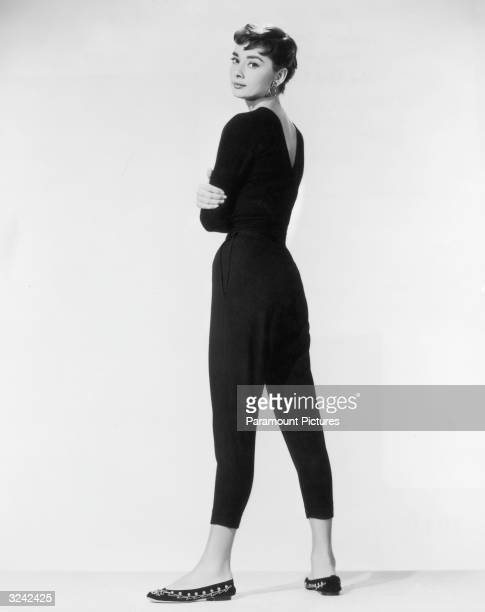 Belgianborn actor Audrey Hepburn wearing black Capri pants and a black sweater with flats looks over her shoulder in a fulllength promotional...