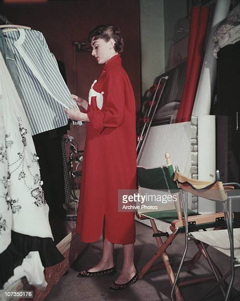 Belgianborn actress Audrey Hepburn browsing through the wardrobe at a photographer's studio circa 1955 She is wearing a full length red coat dress...