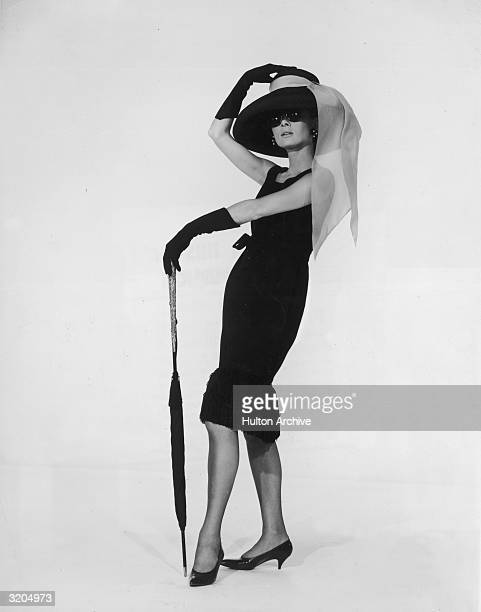 Belgian-born actress Audrey Hepburn in a black cocktail dress designed by French couturier Hubert de Givenchy in a promotional portrait for director...