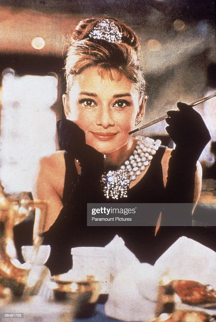 Belgian-born actress Audrey Hepburn (1929 - 1993), in a black, shoulderless dress, matching gloves, and a tiara, smiles with a cigarette holder in her hand, in her role as Holly Golightly the film, 'Breakfast at Tiffany's,' directed by Blake Edwards, New York, New York, 1961.