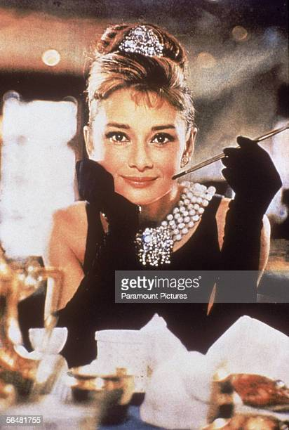 Belgianborn actress Audrey Hepburn in a black shoulderless dress matching gloves and a tiara smiles with a cigarette holder in her hand in her role...