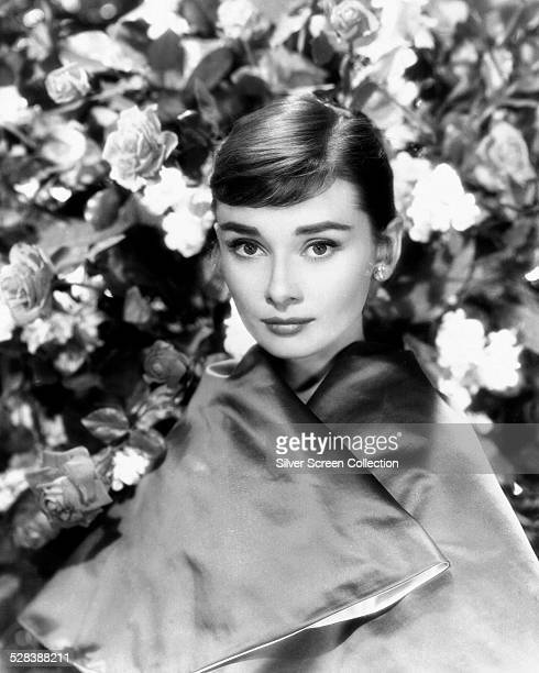 Belgianborn actress Audrey Hepburn posing in a satin wrap with roses in the background circa 1955