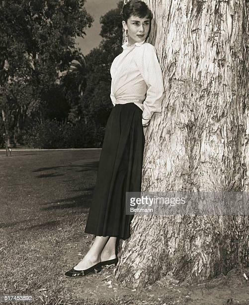 Belgian-born actress, Audrey Hepburn standing against a tree in a publicity photograph circa 1950s.