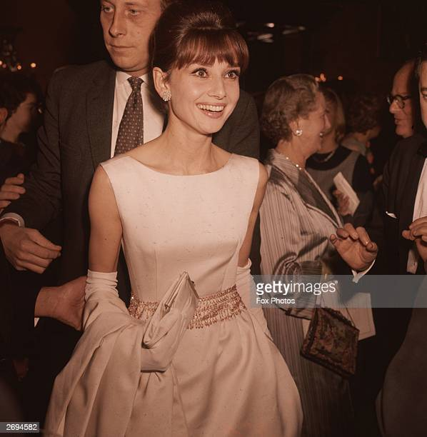 Belgianborn actress Audrey Hepburn wearing a white satin evening gown and long gloves