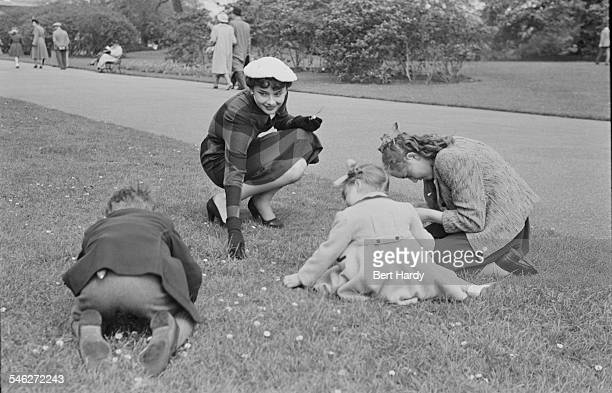 Belgian-born actress Audrey Hepburn with a group of children in Kew Gardens, London, May 1950. She is on a break from rehearsals for the London...