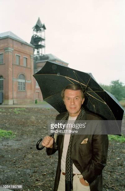 Belgique octobre 2001 Closeup sur Salvatore Adamo chez lui à Uccle avec son épouse Nicole Sous un parapluie à l'extérieur des batiments de la mine