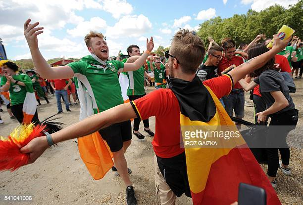 Belgium and Ireland fans embrace as they watch the Euro 2016 group E football match between Belgium and Ireland at the fanzone in Bordeaux on June 18...