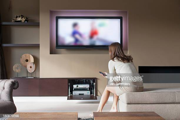 belgium, antwerpen, woman watching television - lcd tv stock photos and pictures