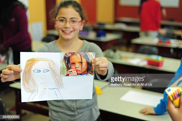 Belgium Asse Basisschool Vijverbeek Art in All of Us Awareness program activities in scool girl with glasses showing picture
