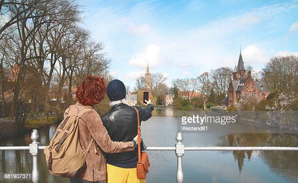 Belgium, Bruges, young couple taking cell phone picture at Minnewater