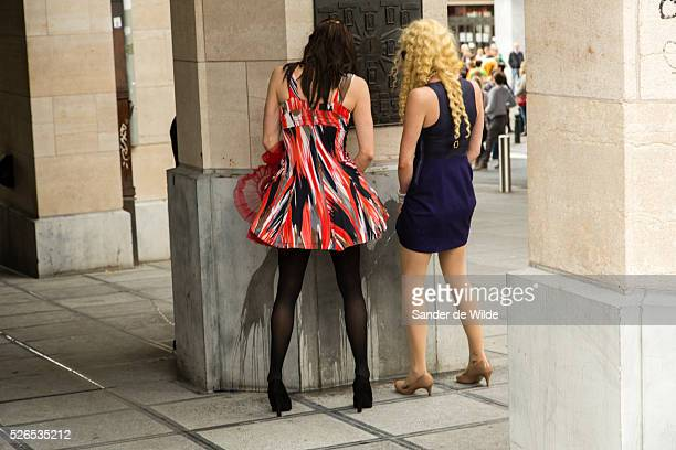 Belgium Brussels 19 May 2013 Two gayman dressed as women pee against a wall during the parade near Central station About 80000 participants at the...