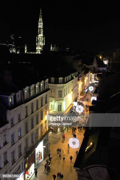Belgium, Brussels, Illuminated street of the city center with the Town Hall Tower in the background